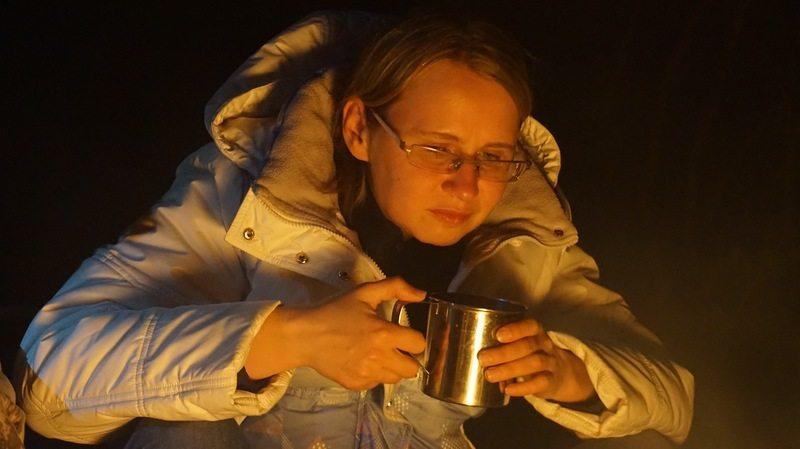 Татьяна у костра, погруженная в свои мысли, согревается горячим чаем