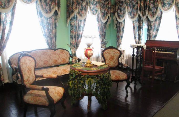 """Купеческая гостиная. На столе лампа в стиле """"модерн"""", у окна - фисгармония"""